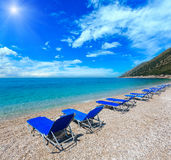 Summer sunshiny pebbly beach. Summer sunshiny pebbly beach with blue sky and sunbeds on beach Albania. Two shots stitch image Royalty Free Stock Photography