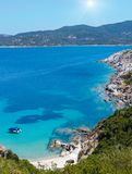Summer sunshiny sea coast Halkidiki, Greece. Summer sunshiny sea scenery with boat in aquamarine transparent water and sandy beach. View from shore Sithonia Royalty Free Stock Image
