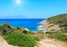 Sunshiny sea coast Sithonia, Greece. Summer sunshiny stony sea coast landscape with Atthos mount view in farHalkidiki, Sithonia, Greece Royalty Free Stock Photography