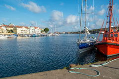 Summer in Sweden. Marstrand, Sweden – July 4, 2014: Pilot boat and a sailboat moored at a quay in Marstrand on a sunny summer morning. Marstrand is a royalty free stock image