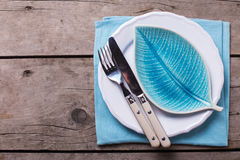Summer  table setting. Decorative plate in form of leaf, knife and fork on white plate Royalty Free Stock Photography