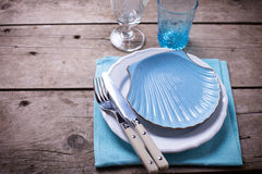 Summer  table setting. Decorative plate in form of shell, knife and fork Royalty Free Stock Images