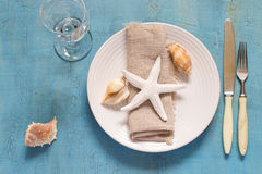 Summer table setting in marine style, decorated with shells.  Stock Photo