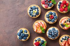Summer tartlets or cake with cream cheese and mixed berry top view. Tasty pastry desserts. Stock Image