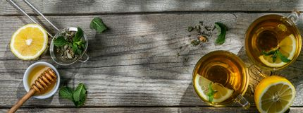 Summer tea - tea cups on rustic wood background with leaves shades - garden Stock Photos