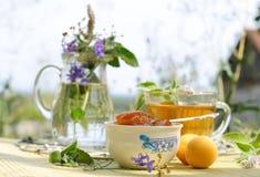 Summer tea time. Apricot jam and mint tea Royalty Free Stock Photos