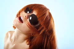 Summer teen girl redheaded in sunglasses over blue. Background Royalty Free Stock Photography