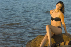 Summer Teen in swimsuit by water. Teen woman in swimsuit sitting on rocks by water at sunset Royalty Free Stock Image