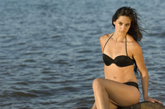 Summer Teen in swimsuit by water. Teen woman in swimsuit sitting on rocks by water at sunset Royalty Free Stock Images