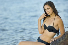 Summer Teen in swimsuit by water. Teen woman in swimsuit sitting on rocks by water at sunset Stock Photography