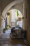 Summer terrace cafe in a narrow arched passageway of Polignano a Mare, Italy. Summer terrace cafe with an old bicycle in a narrow arched passageway of Polignano Royalty Free Stock Image
