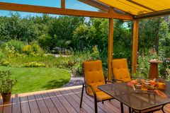 Summer terrace and garden. View from a cozy winter garden in the large natural garden in summer Stock Photos