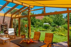 Summer terrace and garden. View from a cozy winter garden in the large natural garden in summer Royalty Free Stock Photo