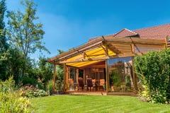 Summer terrace and garden. View from summery nature garden into a cosy winter garden Stock Image