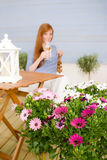 Summer terrace redhead woman hold glass of wine. In garden stock photos