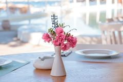Summer terrace of the restaurant. On the tables laying with white plates of wine glasses and white vases with pink royalty free stock photos