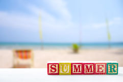 summer text wooden blocks on table with on blur beach Royalty Free Stock Image