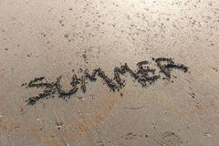 Summer text word on the sand sea beach. Holiday travel concept Royalty Free Stock Photo