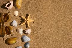 Summer theme background clean sand with sunglasses seashells and starfish royalty free stock photography