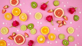 Summer theme background with fruit, citrus and flowers on pink backdrop. Summertime theme background with fruit, citrus and flowers on pink backdrop stock image