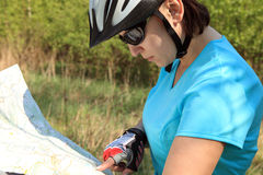 Summer theme. Woman on bicycle reading a map. Stock Images