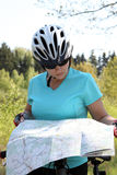 Summer theme. Woman on bicycle reading a map. Stock Image