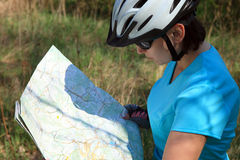 Summer theme. Woman on bicycle reading a map. Royalty Free Stock Photo