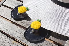 Summer things. White Hat and slippers with ananas are on the table. royalty free stock photo