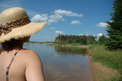Summer time. A girl looking at lake wearing straw hut stock photography