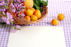 Summer time!. Beautiful basket with wild flowers and fruits at the violet tablecloth royalty free stock images