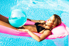 Summer time. Young woman on water bed in swimming pool Stock Photography