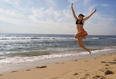 Summer Time. Pretty young girl is jumping up in  the air at the beach Stock Images