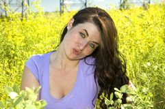 Summer time. Attractive woman sitting in a field of yellow flowers Stock Image