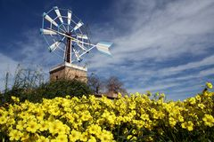 Summer Time. Windmill and yellow flowers scene Stock Photo