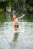 Summer time. Boy running in water and making splashes Stock Photo