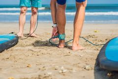 Summer time and active rest concept. Young surfer man beginner fastens leash across leg, going to surf on big barral royalty free stock images