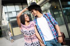 Beautiful young couple enjoying in good mood in city. Lifestyle, love, dating, vacation concept. Summer time. Beautiful young african couple dating and smiling royalty free stock images