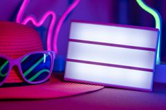 Summer time with blank light box on hat with sunglasses refection flamingo and cactus neon pink and blue and green light on table stock images