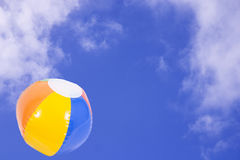 Summer Time. Blue skys with fluffy white clouds and a colourfull beachball Stock Photos