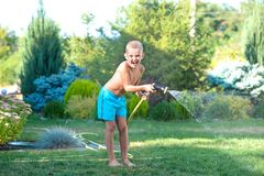 The boy splashes with a garden hose in the garden. Summer time. Summer time.The boy splashes with a garden hose in the garden stock image