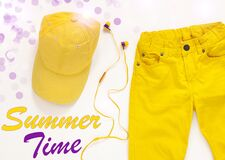 Yellow flatlay jeans, baseball cap and headphones on white background card,top view.Summer Time background