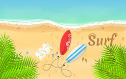 Summer time and favorite surfing. Surfboards, slippers and a towel lie on the beach. Beautiful text on the sand. A bright, sandy b Royalty Free Stock Photos