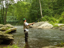 Summer Time Fishing. Photo of man fishing the deep pools below Falls Road bridge on the Gunpowder river for trout during summer.  The Gunpowder is one of Royalty Free Stock Photography