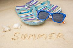 Summer time. Flip-flops on seashore, seashell, sunglasses Royalty Free Stock Photo