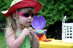Summer Time Fun. Colorful picture of a young girl fixing her sunhat Royalty Free Stock Photo