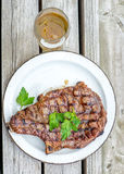 Summer time fun in the backyard. Flame grilled rib eye beef steak on weathered wood table. Stock Image