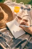 Summer time -  hands with pen writing on notebook in the park.  royalty free stock image