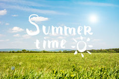 Summer time lettering with sky and grass background. Royalty Free Stock Photo