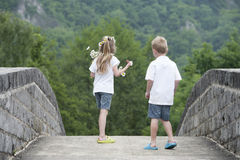 Summer time : little boy @ girl running on a bridge Stock Images
