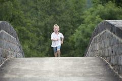 Summer time : little boy running on a bridge Stock Images